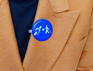 Blaue Ansteckklemme mit Symbol für Taubblindheit in weiß: ein Ohr, ein Plus und das internationle Symbol für Sehbehinderung. Dier Button ist an einem orangen Blazer angebracht.