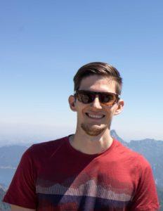 Bild von Gerald. Er trägt Sonnenbrillen und steht auf einem Berg. Dahinter Landschaft und blauer Himmel.