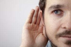 Das halbe Gesicht eiens Mannes ist zu sehen. Er hält eine Hand hinter sein rechtes Ohr.